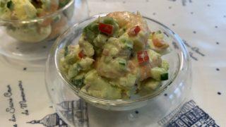 丸くて深い透明なガラスのお皿に盛りつけられた色鮮やかなアボカドとエビのサラダ